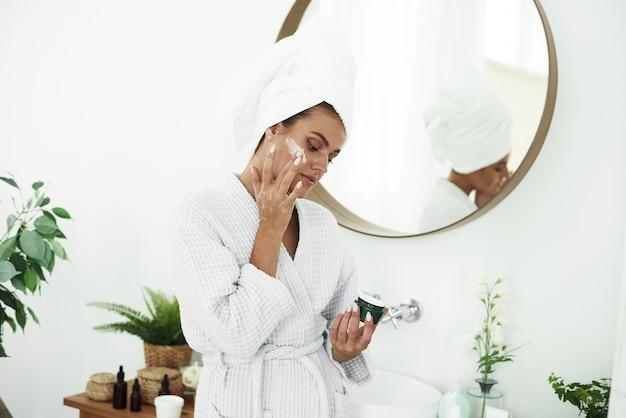 화장실에서 그녀의 얼굴에 로션을 적용 젊은 웃는 여자의 초상화. 미용술. 아름다움과 스파.