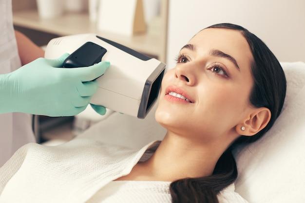 베개에 누워 웃고 있는 젊은 여성의 초상화와 현대적인 도구의 도움으로 그녀의 피부에 대한 전체 개요