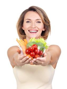Портрет молодой улыбающейся женщины с тарелкой овощей, изолированных на белом.