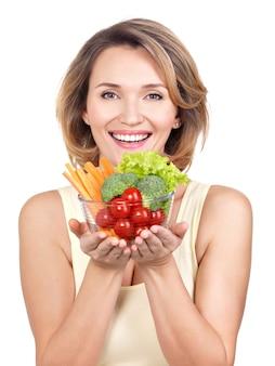 野菜のプレートを持つ若い笑顔の女性の肖像画-白で隔離。