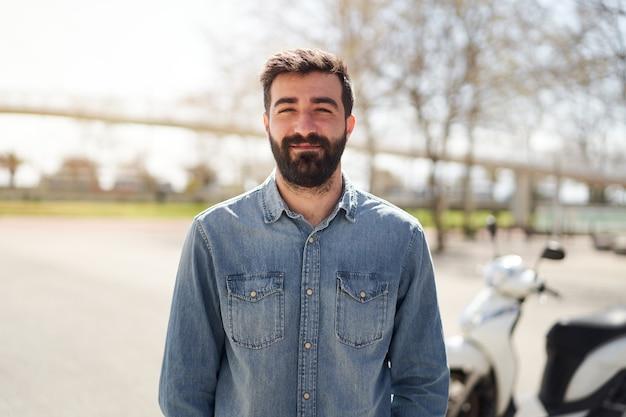 Портрет молодого испанца, смотрящего в камеру, мужчина с веселой улыбкой стоит перед его ...