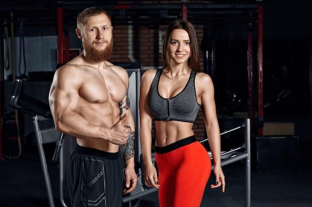 Портрет молодой пары спорта в спортзале