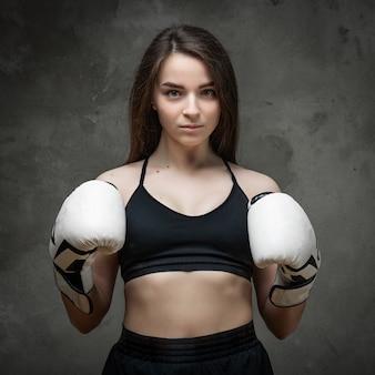 짧은 상단과 권투 장갑에 젊은 낚시를 좋아하는 여자 권투 선수의 초상화는 선반에 그의 손을 보유하고 어두운 회색 배경에 포즈