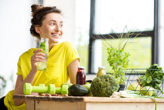 健康的な食べ物とダンベルをテーブルに置いて屋内に座っている黄色のtシャツを着た若いスポーツ女性の肖像画