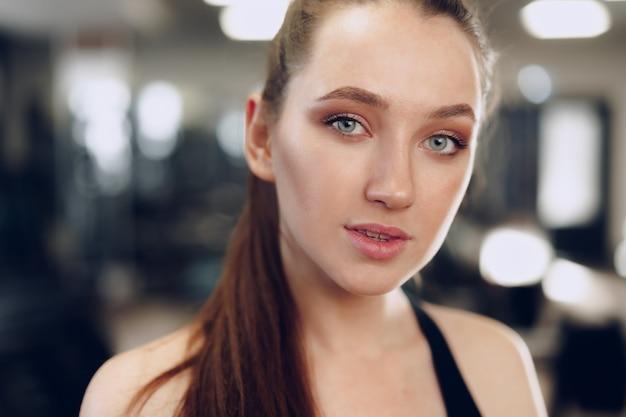 フィットネスクラブでトレーニング若いスポーティな白人女性の肖像画