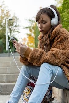 계단에 앉아 젊은 학생 여자의 초상화. 음악을 듣고 있습니다.