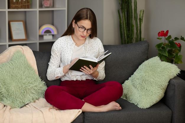 本を読んでいる若い学生の肖像画。自宅のベッドで本を読んで美しい若いブルネットの女性