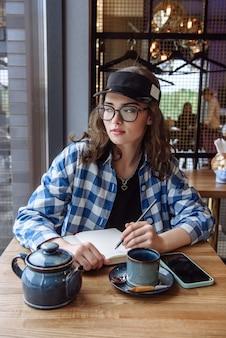 레스토랑의 테이블에 앉아 공책에 글을 쓰는 세련된 젊은 브루네트 여성의 초상화