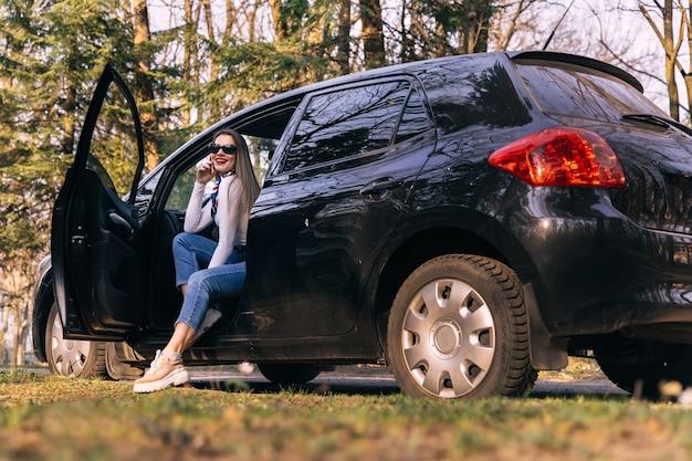 Портрет молодой стильной женщины, путешествующей на черной машине, сидящей на водительском сиденье на загородной дороге в лесу