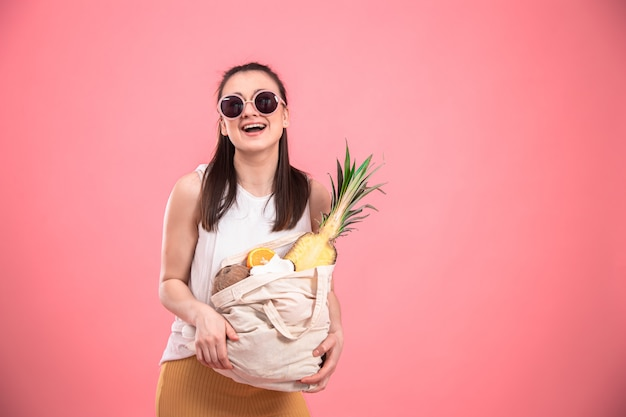 Портрет молодой стильной женщины с эко-фруктовой сумкой