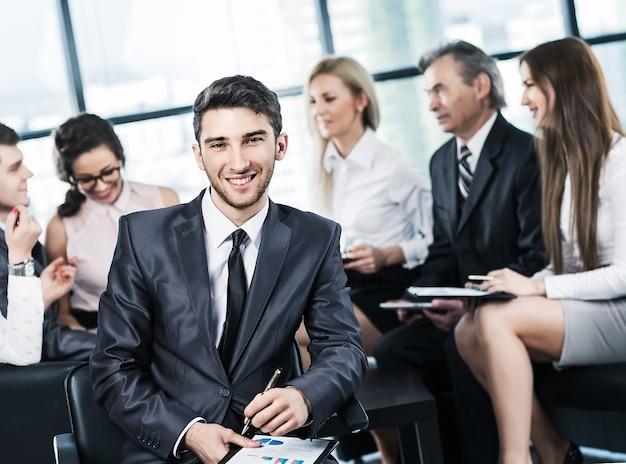 Портрет молодого успешного менеджера-директора крупным планом на рабочей бизнес-команде в современном офисе