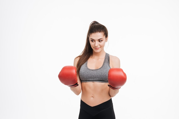 分離されたボクシンググローブを身に着けている若い驚いたフィットネス女性の肖像画