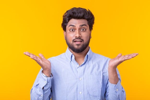Портрет удивленного молодого человека в рубашке, дозирующего у желтой стены