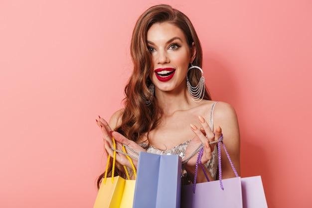 Портрет молодой удивленной потрясенной позитивной женщины в ярком платье с пайетками, изолированном над розовой стеной, держащей хозяйственные сумки.