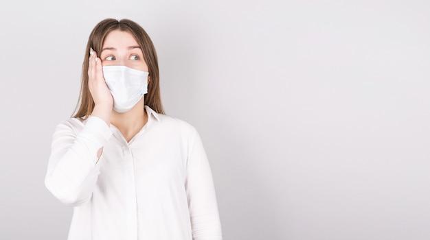 회색 배경 위에 절연 의료 마스크에 젊은 놀된 여자의 초상화. 어린 소녀 환자는 옆으로 찾고 벽 배경에 대해 서, 텍스트 복사 공간