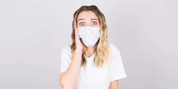 회색 배경 위에 절연 의료 마스크에 젊은 놀된 여자의 초상화. 어린 소녀 환자는 그녀의 눈에 벽 배경 wirh 두려움, 텍스트 복사 공간에 대해 서