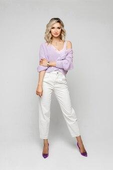 Портрет молодой высокой женщины со светлыми волнистыми волосами средней длины в бледно-лиловом свитере или оверсайз-пуловере