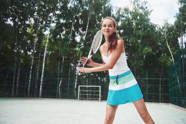サーブの準備ができて立っている若いテニス選手の肖像画。