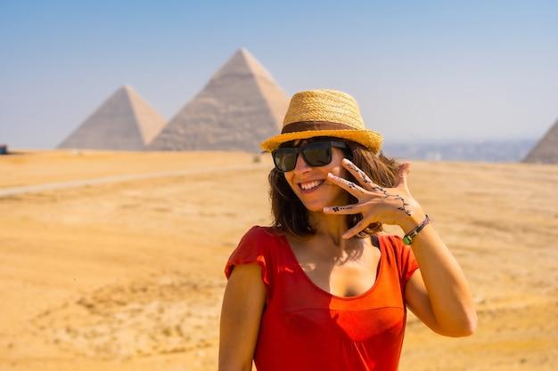世界最古の葬儀の記念碑であるギザのピラミッドを楽しむ赤いドレスを着た若い観光客の肖像画。エジプト、カイロ市