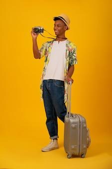 孤立した背景の上にカメラで写真を撮る若い観光客の男性の肖像画。旅行のコンセプト。
