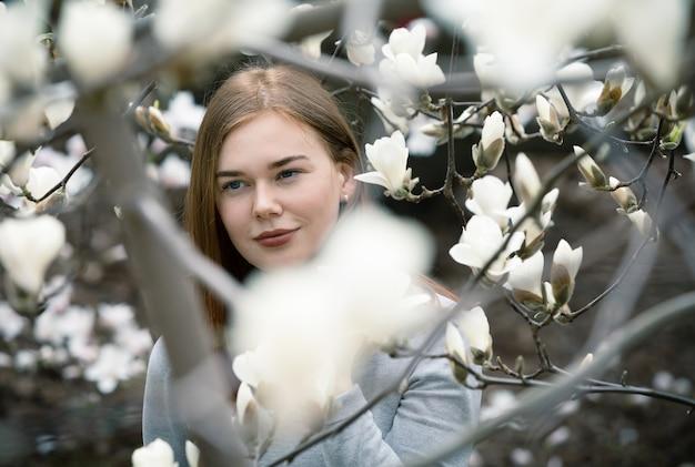 키예프 식물원에서 꽃이 만발한 목련 나무 사이에서 젊은 여자의 초상화. 꽃이 만발한 목련 나무는 매년 봄 수천 명의 방문객을 끌어들입니다