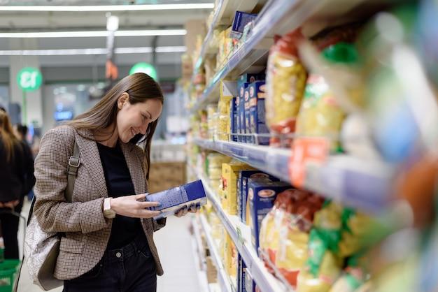 Портрет молодой женщины на стороне супермаркета читает этикетку макарон в упаковке
