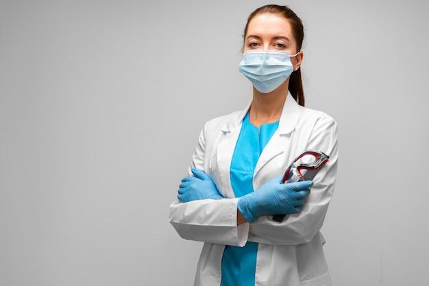 マスクを身に着けている若い女性医師または医療従事者の肖像画をクローズアップ