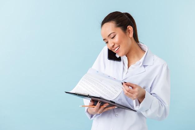 携帯電話で話しているクリップボードを保持している青い壁の上に孤立してポーズをとる若い女性医師の肖像画。