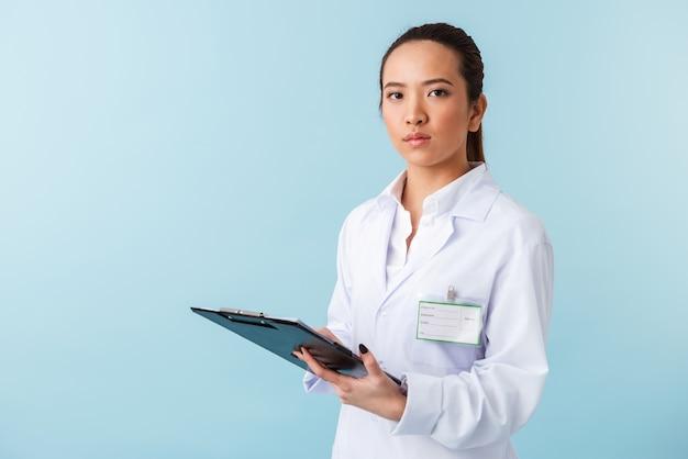 クリップボードを保持している青い壁の上に孤立してポーズをとってポーズをとる若い女性医師の肖像画。