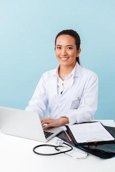 Портрет молодой женщины-врача, позирующей изолированной над синей стеной, с помощью портативного компьютера.
