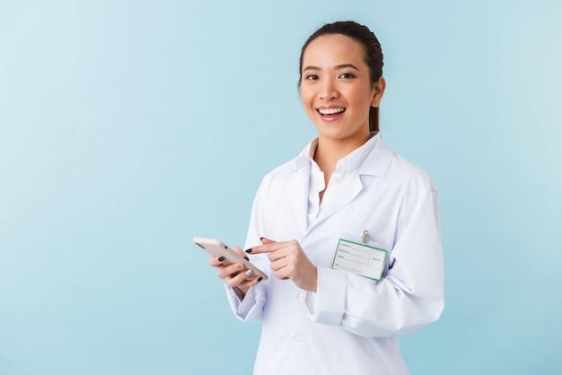 携帯電話を使用して青い壁の上に孤立してポーズをとってポーズをとる若い女性医師の肖像画。