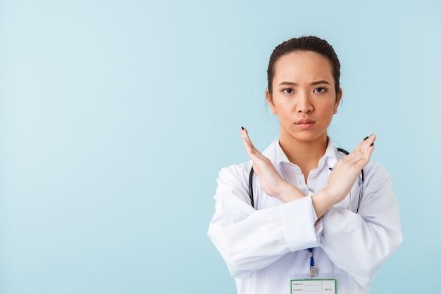 停止ジェスチャーを示す聴診器で青い壁の上に孤立してポーズをとる若い女性医師の肖像画。