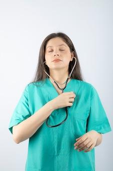 制服を着た聴診器を持つ若い女性医師の肖像画。