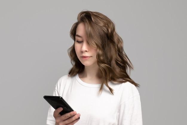 携帯電話、灰色の背景、コピースペースを使用して白いtシャツを着た若い女性の肖像画。スマートフォンを見下ろす美しい白人の女の子。オンラインチャット、メッセージングの概念