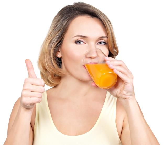 젊은 여자의 초상화는 흰색 절연 오렌지 주스를 마신다.