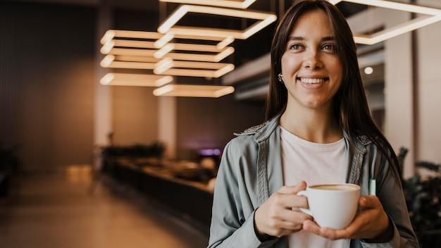 Портрет молодой женщины, наслаждающейся кофе