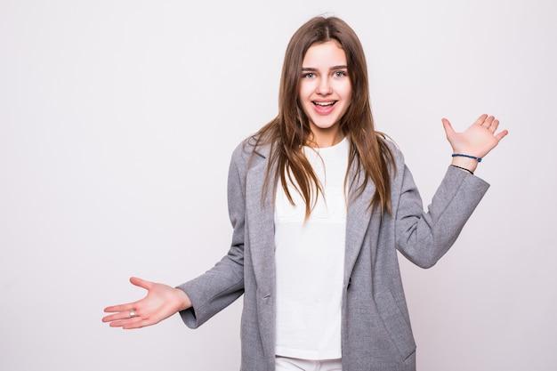 灰色の背景上の成功で興奮している若い女性の肖像画。
