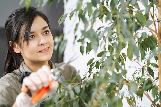 Портрет молодой женщины-садовника, удаляющей сухие ветки с комнатного растения с помощью секатора дома