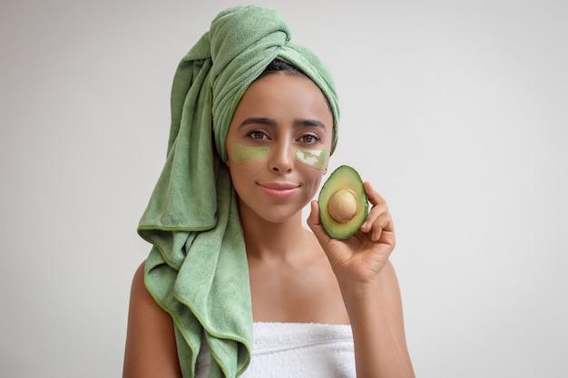 Портрет молодой женщины, держащей в руке половину авокадо