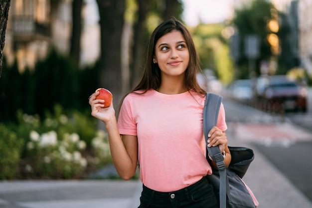 通りの背景にリンゴを保持している若い女性の肖像画