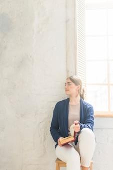 家庭のスツールに座っている本を持っている若い女性の肖像