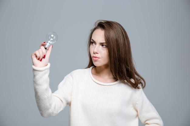 Портрет молодой женщины, держащей лампочку на сером фоне