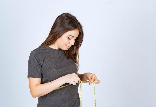 彼女の腰の周りに巻尺を保持している若い女性の肖像画