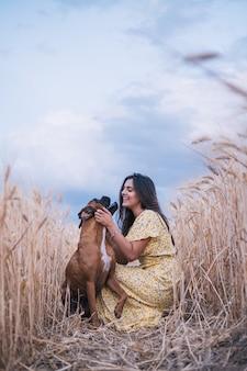 Портрет молодой женщины, обнимающей ее собаку посреди пшеничного поля. концепция природы и животных