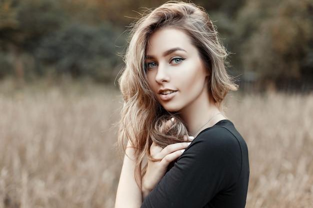 Портрет молодой женщины в черной рубашке на природе