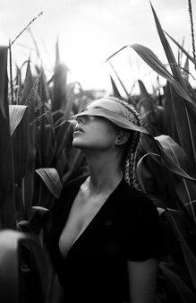 彼女の顔が葉で覆われているトウモロコシ畑の若い女性の肖像画