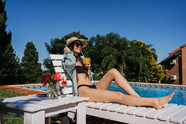 プールの端に座ってジュースを飲む帽子をかぶった若い女性の肖像画。