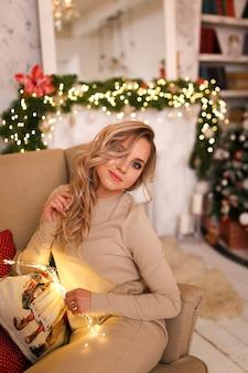 ホームドレスと暖かい靴下を身に着けている若い女性の肖像画は、暖炉とクリスマスツリーのそばでリラックスします