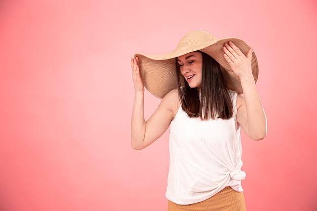 ピンクの背景に、大きな夏の帽子と白いtシャツを着た若い女性の肖像画。夏のルックのコンセプト。