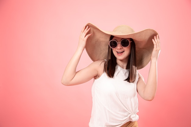 大きな夏の帽子とメガネ、ピンクの背景の若い女性の肖像画。夏のコンセプトです。